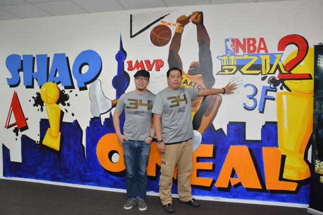 两位制作人在手绘的欧尼尔涂鸦墙前合影